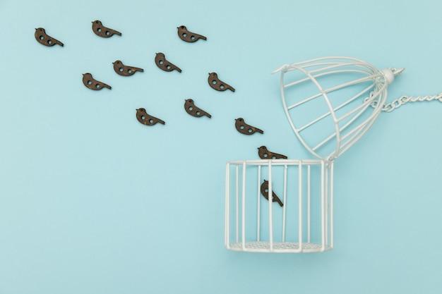 Птицы вылетают из белой клетки на синем фоне