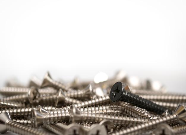 Черный винт в кучу серебряных винтов на белом фоне с копией пространства