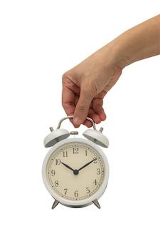 白で隔離される白のビンテージの目覚まし時計を持っている手