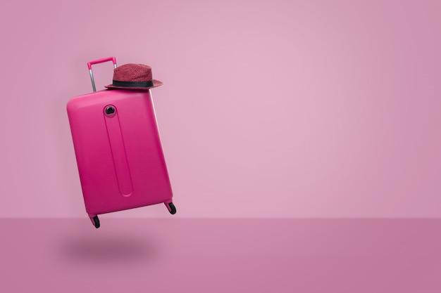 パステル調のピンクの背景の帽子とピンクのスーツケース。旅行のコンセプトです。