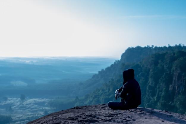 Человек сидит и смотрит на восход солнца на скале