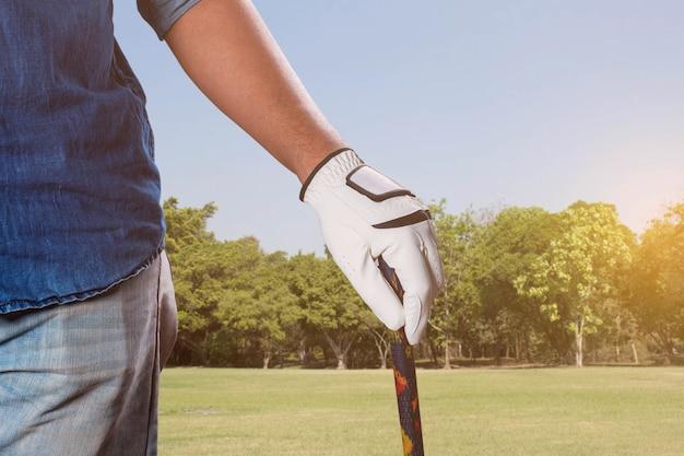 芝生でゴルフをしている男。