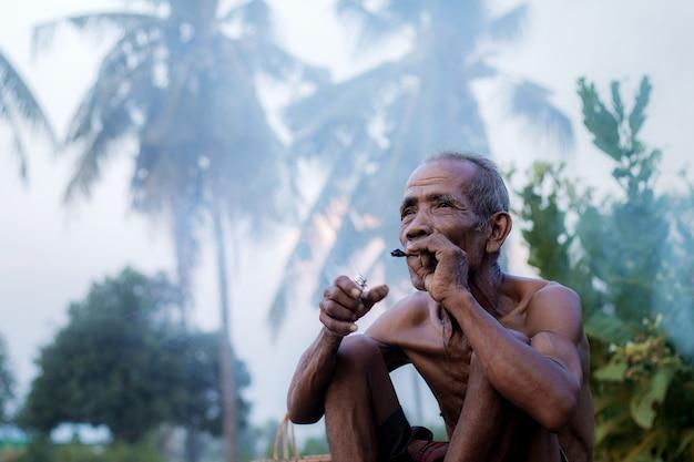 Старик курит на поле.