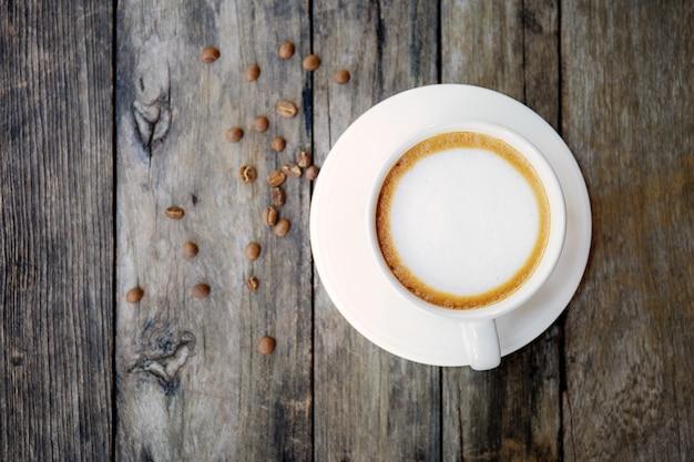 Кофейная чашка и семя на древесине.
