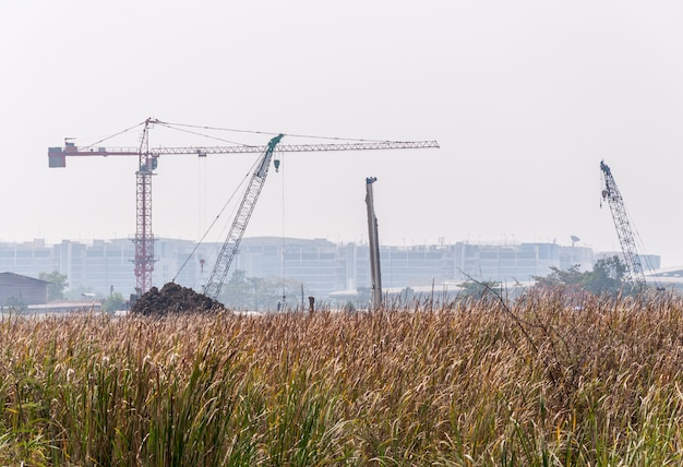 Высокий кран и дрель работают на строительной площадке.