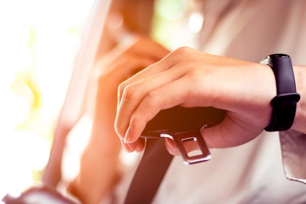安全ベルト安全を最初に車の中でシートベルトを固定する人のクローズアップ