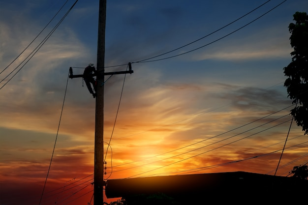 電気技師の高電圧労働者のシルエットは、夕方に停電を修正するために働いています。