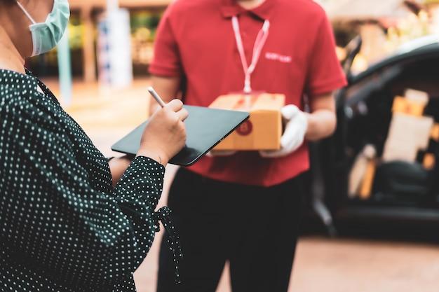 女性は家の前で宅配便から小包を受け取った後にデジタル携帯電話にサインインするので、病気の蔓延を防ぐためにマスクを着用する必要があります。