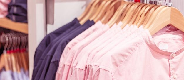 ショッピングモールのデザイナー衣料品店の棚に掛かっている服。