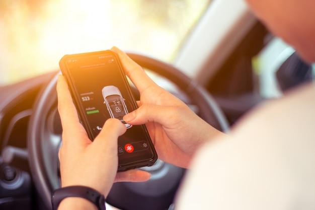 スマートフォンでアプリを制御して駐車場に駐車する自動運転車。