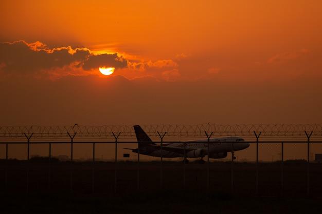 滑走路、夕日と飛行機