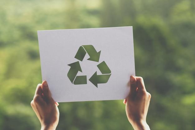 両手で世界のエコロジー概念環境保全を保存紙のリサイクル表示をカット