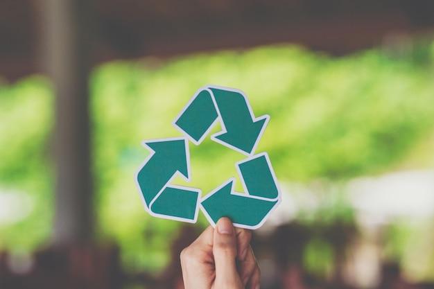 両手でエコロジー概念環境保全紙のリサイクル表示をカット