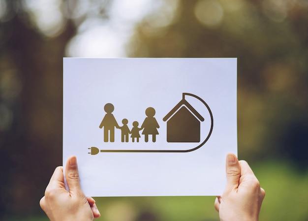 両手をカット紙地球愛するエコロジー家族を示す