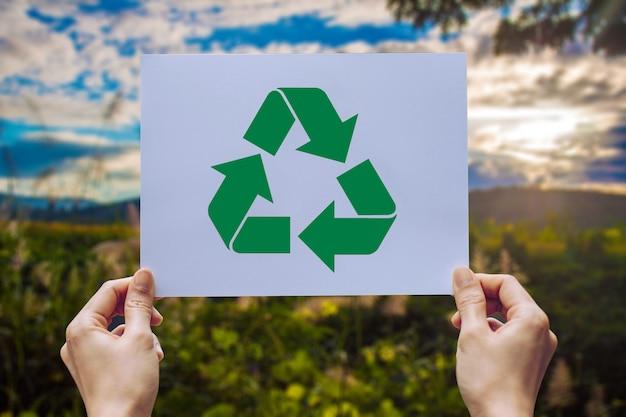 保持している世界のエコロジー概念の環境保護を保持する手で紙リサイクル表示をカット