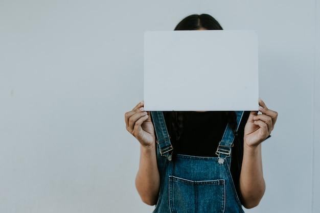 空の紙、立っている深刻な若いアジア女性を保持している女の子