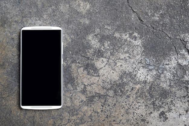 セメント床にスマートフォンの空白の黒い画面