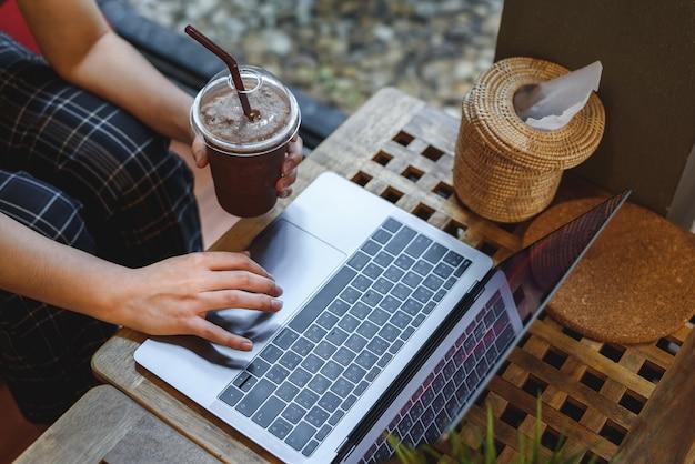 女の子がカフェでキーボードを入力する