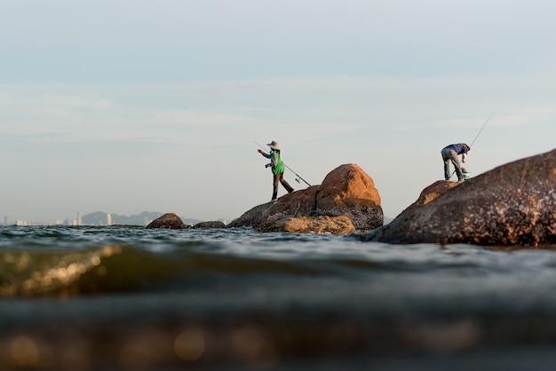 海の岩の漁師のシルエット