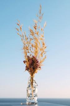 Букет из сушеных цветов бессмертника и осенней травы в деревенской стеклянной бутылке на фоне моря