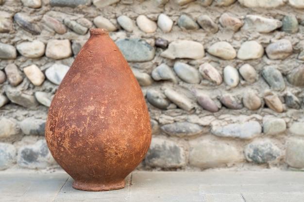 Старый квеври на каменном фоне, грузинские глиняные сосуды для вина.
