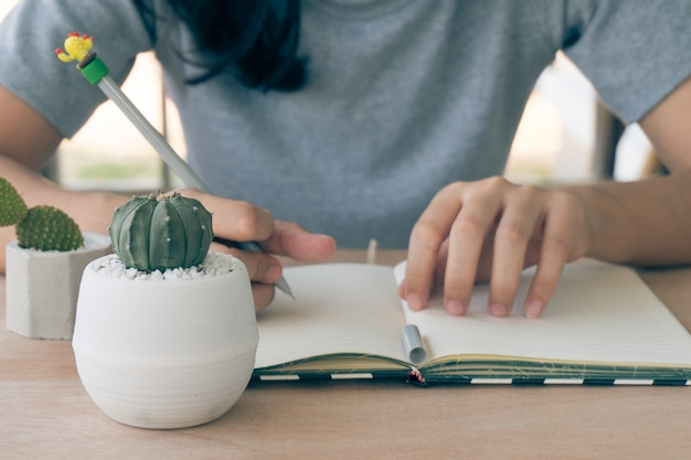 Крупным планом зрения женщины изучение и уход кактус на деревянный стол в доме выращивания кактусов, питомник кактус