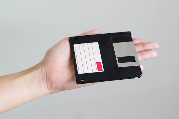 黒のフロッピーディスクを持っている手