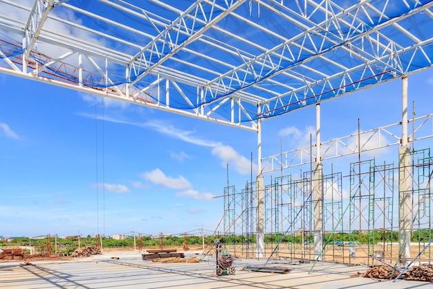 青い空の背景に建設工事のための鋼の屋根フレームの構造。