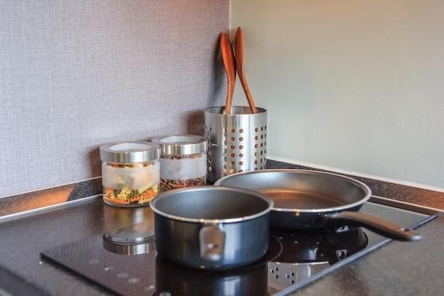 Черная кастрюля на верхней панели индукционной печи в современной кухне для приготовления пищи, крупным планом