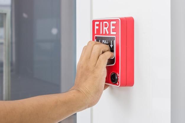Рука человека потянув выключатель пожарной тревоги на белой стене в качестве фона для аварийного случая