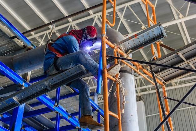 ティグ溶接機を使用して保護マスク溶接金属配管を持つ産業労働者