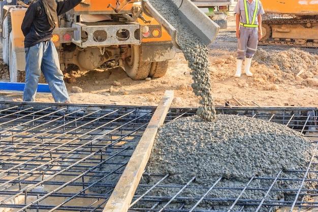 Бетонные заливки во время коммерческих бетонных полов зданий на строительной площадке.