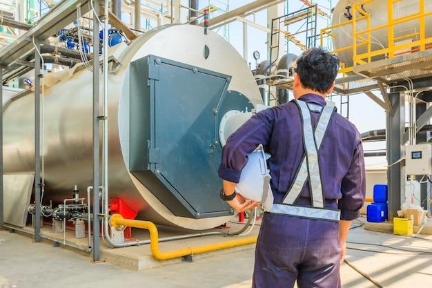 ボイラールーム内の暖房装置のガスボイラーで作業するメンテナンスエンジニア
