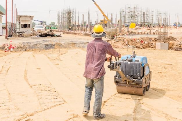 道路建設作業中の道路ローラー中の建設労働者。