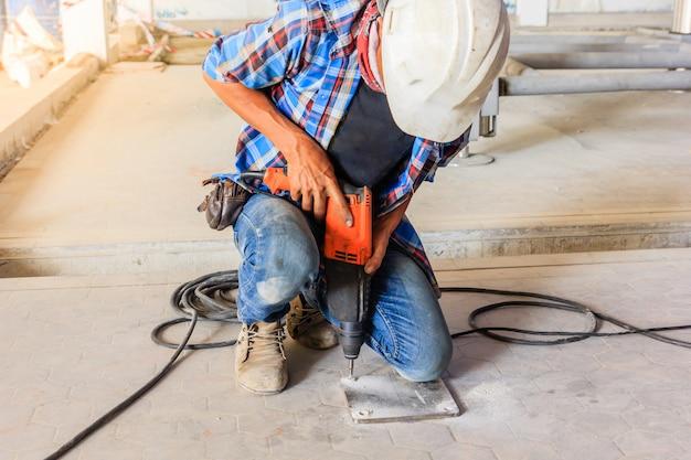 電気ドリルを使用して工事現場に鋼板を設置する建設作業員。