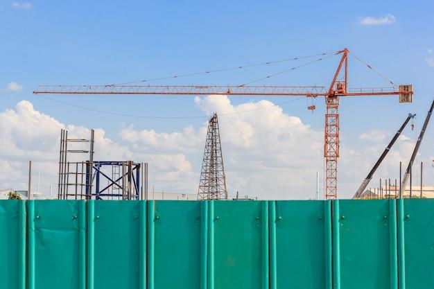 工事現場での建設工事のクレーンと青空に対する建物