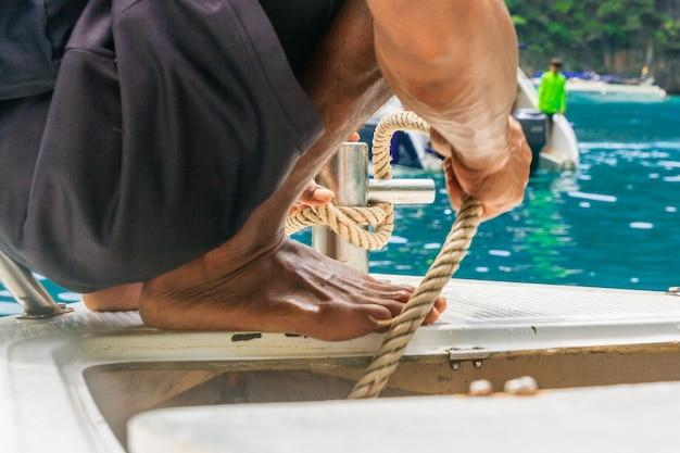 若い男は海にアンカーを、ボートにはスチールのアンカーの周りに結ばれた係留ロープを置く