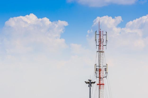 Радиотелефонная антенна и спутниковая башня с голубым небом