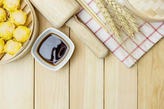 木製のテーブルの背景に竹のバスケットで蒸し餃子(中国のダムサム)