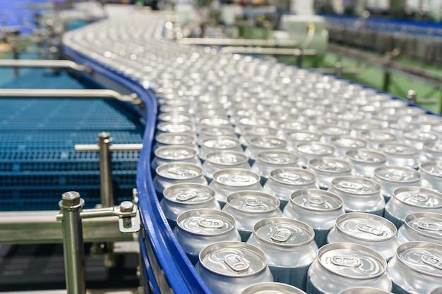 工場で何千ものアルミニウム飲料缶を運ぶコンベヤーライン。