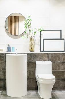 Современный интерьер ванной комнаты с современной раковиной, туалетом и зеркалом