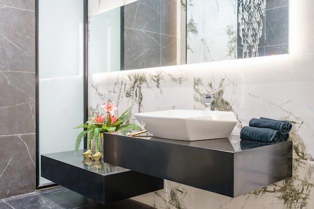 洗面台蛇口と鏡付きのバスルームのインテリア