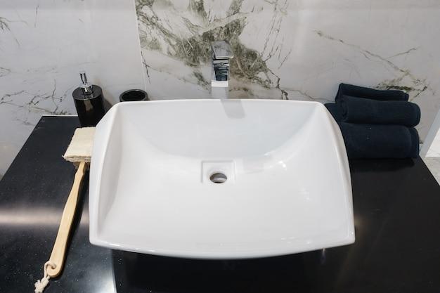 洗面台の蛇口と鏡付きのバスルームのインテリア。バスルームのモダンデザイン