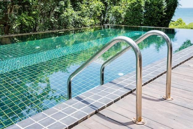 青いプールでバーのはしごをつかむ