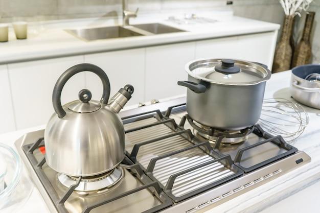 ステンレス鋼の鍋と家庭の台所でガスコンロで沸騰するやかんのクローズアップ