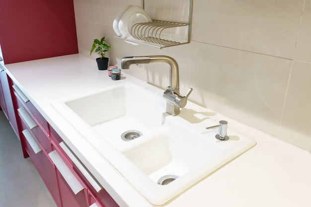 ステンレスの台所の流しおよび台所の水道水。作り付けの電気器具。キッチン家電