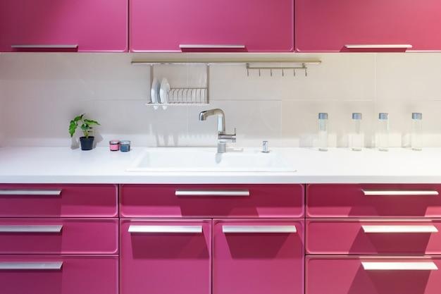 ステンレスの台所の流しおよび台所の水道水。作り付けの電気器具。