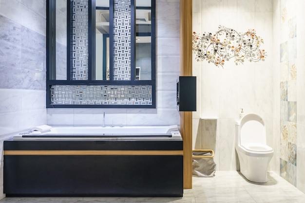 ミニマルなシャワーと照明、白いトイレ、洗面台、バスタブ付きのモダンなバスルームのインテリア