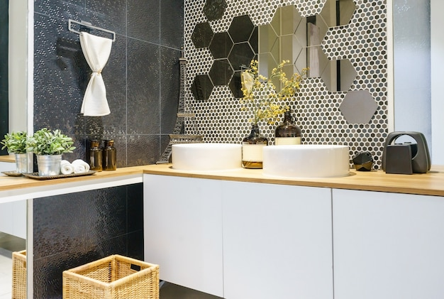 トイレと洗面台付きの明るいタイル張りのモダンで広々としたバスルーム。