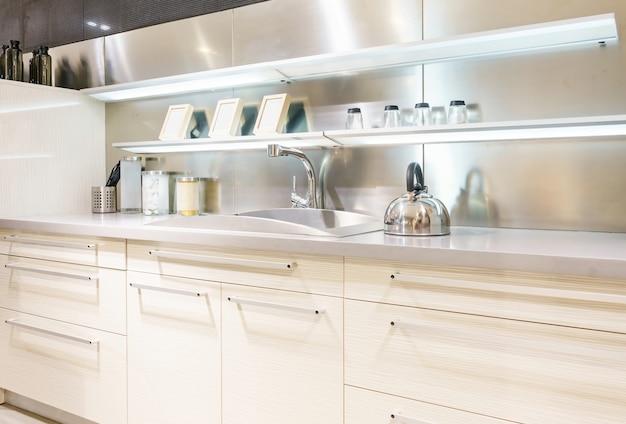 ステンレスの台所の流しおよび台所の水道水。作り付けの電気器具。キッチン家電。